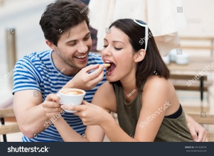 stock-photo-romantic-young-couple-drinking-coffee-with-the-young-man-laughingly-feeding-a-biscuit-to-his-201458534